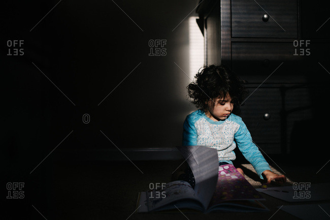 Young girl with messy hair sitting on floor playing with stickers