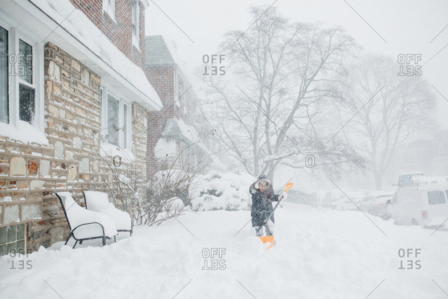 Young girl outside with snow shovel in blizzard