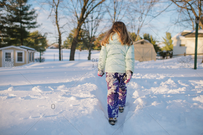 Girl with snow-covered pants walking through a path in the snow