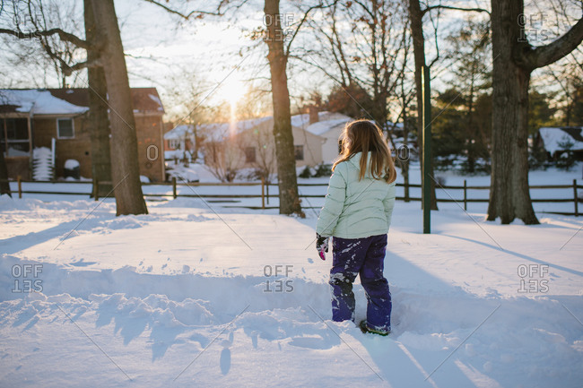 Back view of girl walking outside in the snow