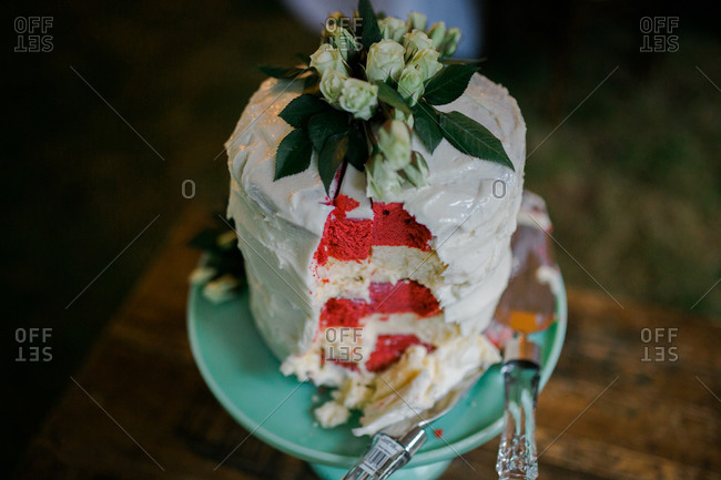 Red and white wedding cake with a slice cut out of it