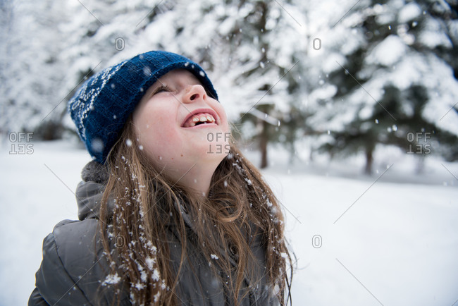 Happy young girl looking up at the snow falling