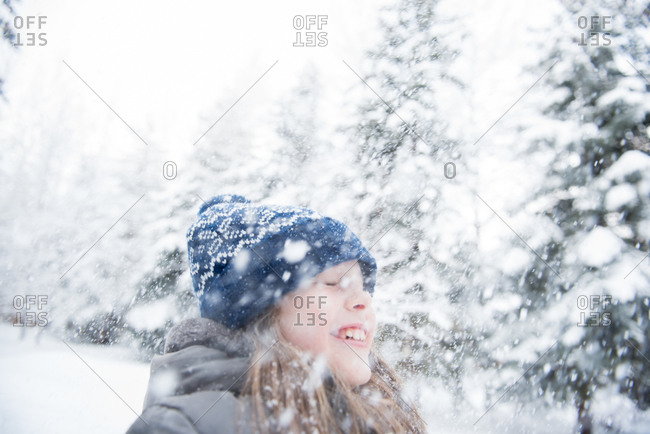 Young girl smiling as snow falls on her