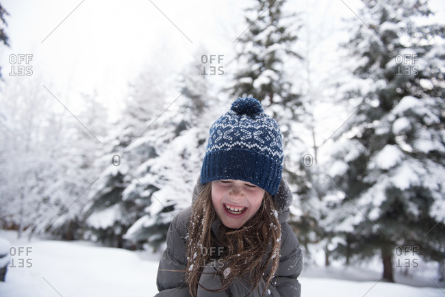 Laughing girl in blue knit had outside during snowfall