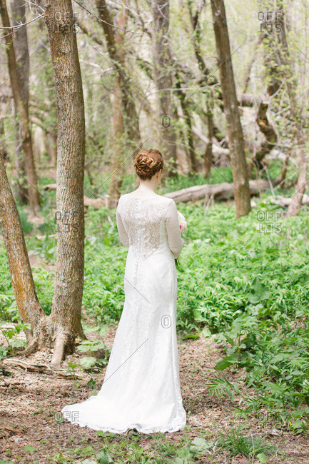 Bride in a button back lace wedding gown standing in the woods