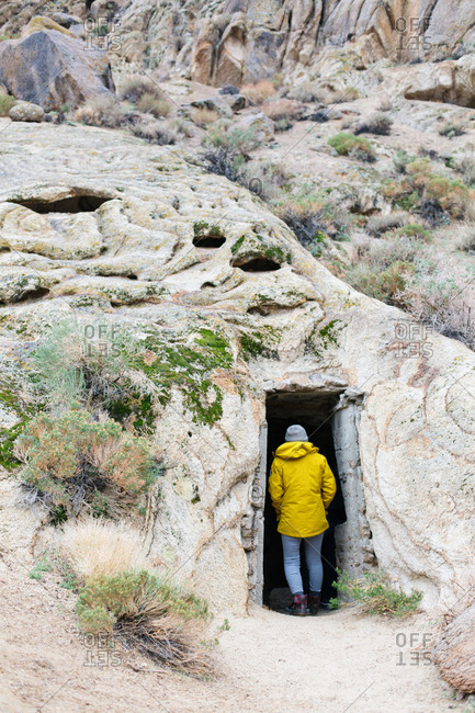 Woman in yellow jacket standing in doorway that leads into hillside