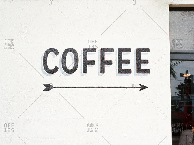 Coffee sign painted on white wall with arrow pointing to caf� door