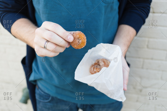 Man holding a bag of sugary mini donuts
