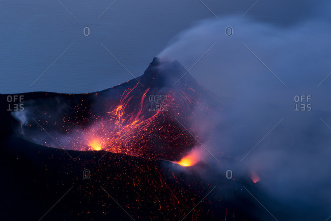 Glowing lava projectiles explode out of a volcano on the Aeolian Islands in Italy