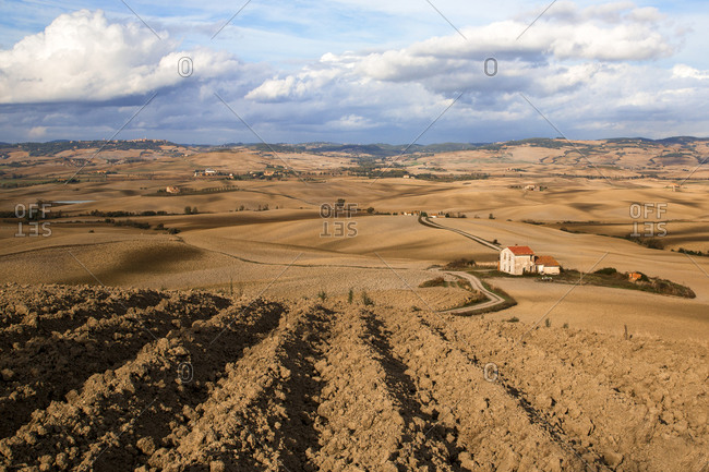 Furrowed expanses of farm fields in Val D'Orcia, Tuscany, Italy
