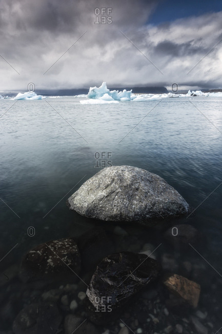 Rocks near the shore of a glacial lake with icebergs in Southern Iceland