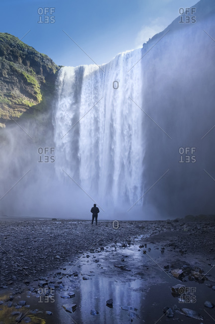 Person silhouetted at base of the waterfall of Skogafoss located in the South of Iceland