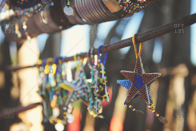A star shaped piece of Maasai jewelry hanging in the sunlight