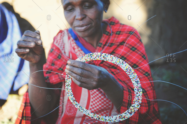 Tanzania - July 15, 2015: Maasai villager finishing a beaded necklace