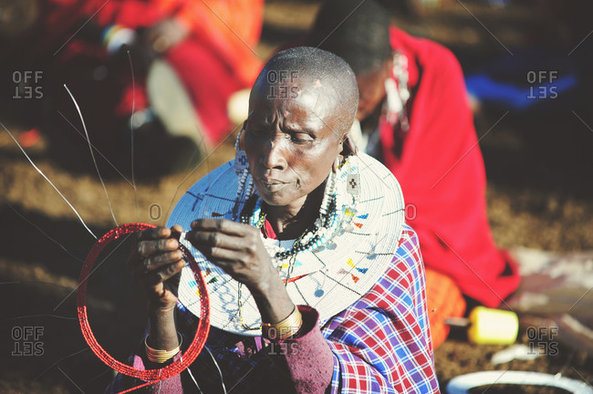Tanzania - July 15, 2015: Maasai villager finishing a piece of beaded jewelry