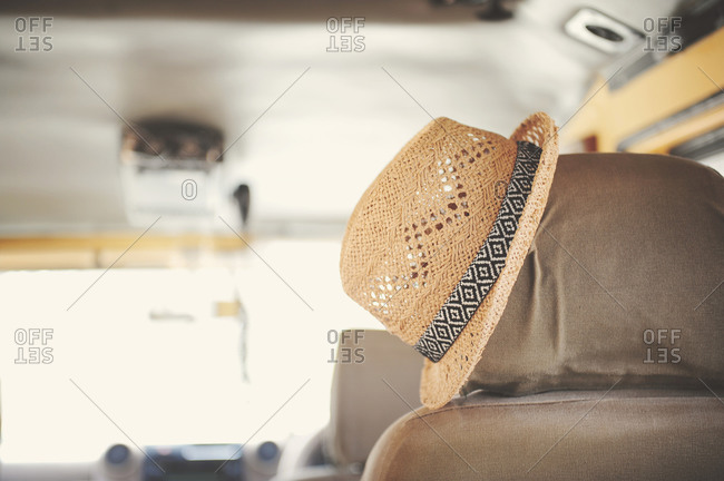Straw hat hanging on the headrest of a seat