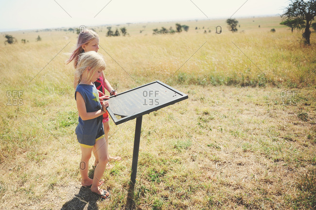 Girls reading a plaque in the African Serengeti