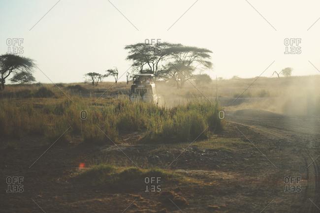 Safari truck driving down a dusty road