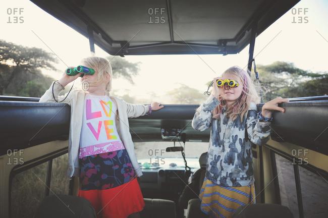 Girls riding through rural Africa looking through binoculars