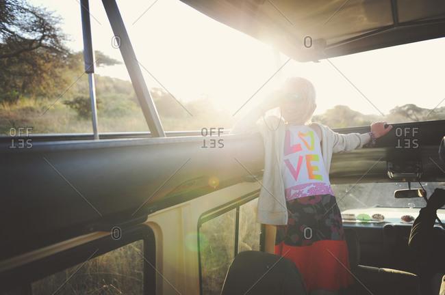 Girl riding through rural Africa looking through binoculars