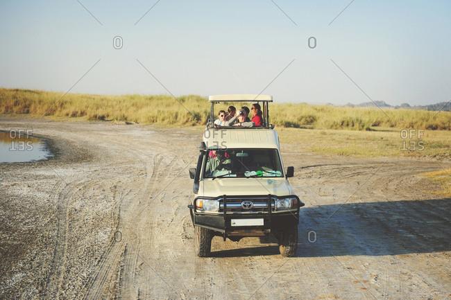 Tanzania - July 19, 2015: Safari truck driving through a dry wash in the Serengeti