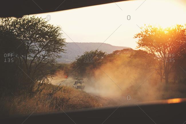 Safari truck driving down a dusty road near sunset