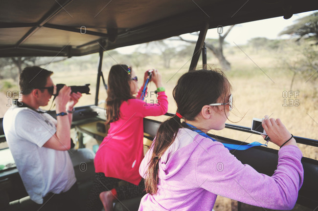 Father photographing wildlife with his daughters on safari in the African Serengeti