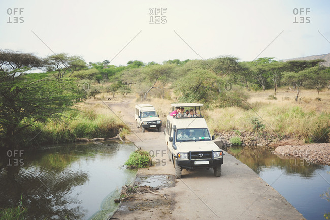 Tanzania - July 20, 2015: Safari trucks driving over a small bridge across a wash in the African Serengeti
