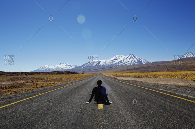 Man sitting in the middle of a desert highway gazing at distant mountains