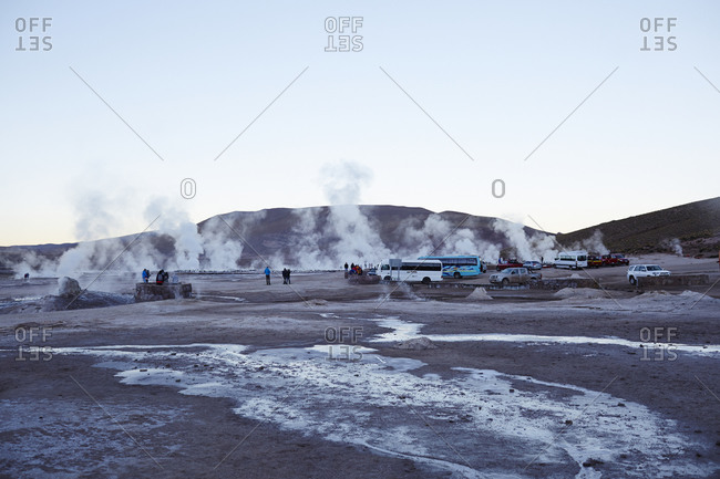 Tourist buses gathering at dawn at a geyser field