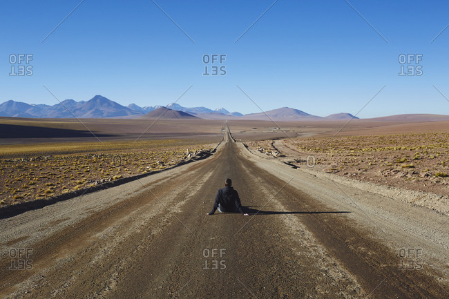 Man sitting in the middle of a dirt road leading across a desert