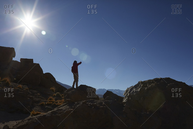 Silhouette of a man climbing a boulder stack in desert mountains