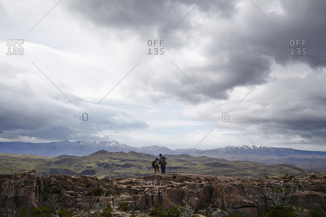 Two hikers admiring the view from a mountain ridge
