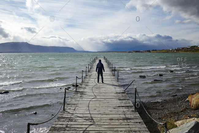 Man on a pier on a choppy lake in the afternoon sun