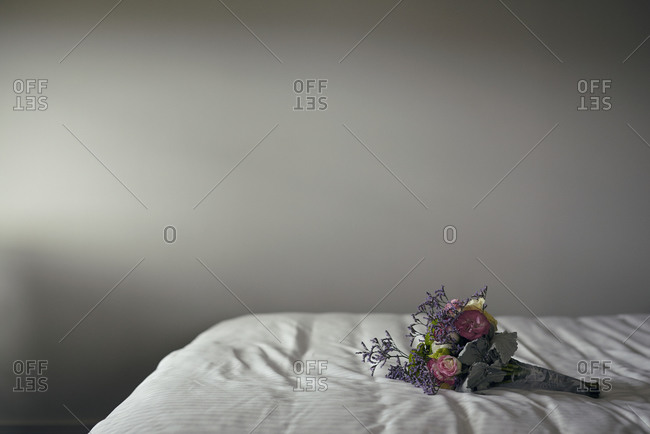 A wedding bouquet of flowers on a bed