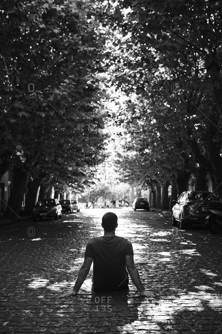 Man sitting in the middle of a tree-lined street, Colonia del Sacramento, Uruguay