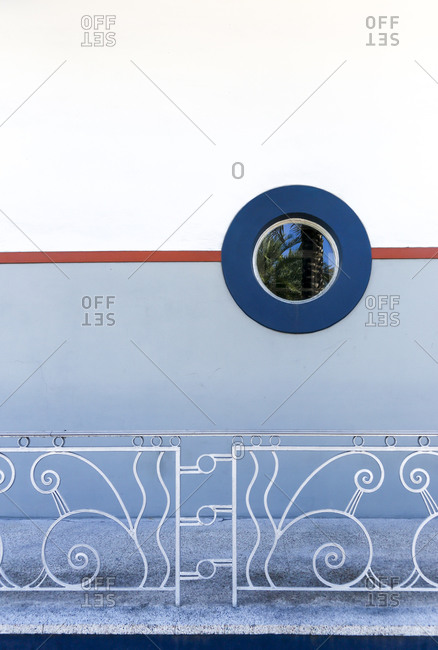 Round window and iron fence on building exterior in South Beach, FL