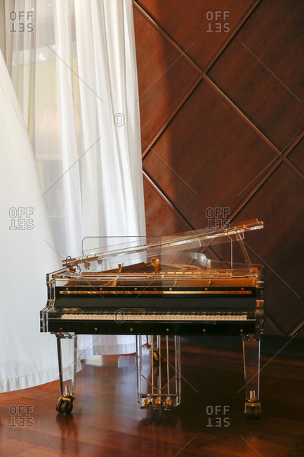 Vintage piano by flowing curtains