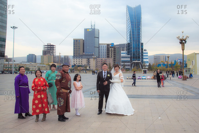 Ulaanbatar, Mongolia - September 21, 2013: Family in traditional clothing poses with bridge and groom