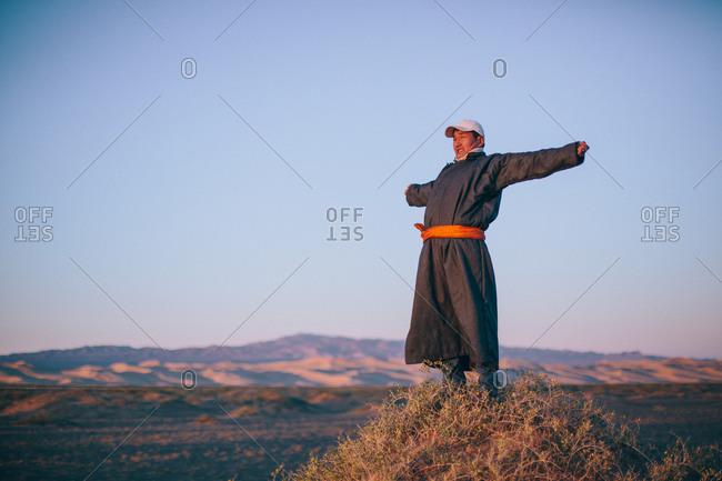 Mongolia - September 26, 2013: Mongolian man stretches as the sun rises in the Gobi Desert