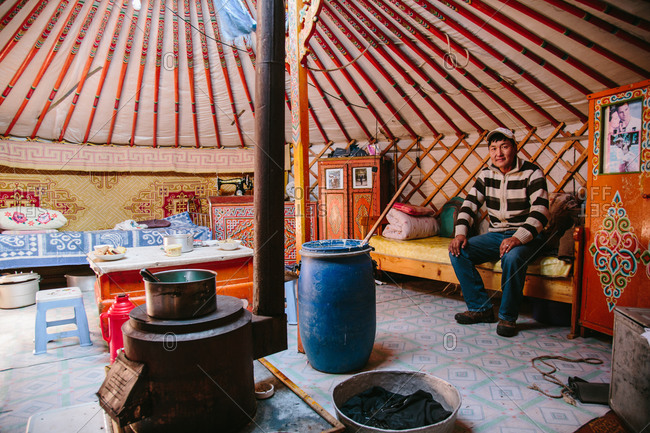 Mongolia - September 28, 2013: Man sitting in interior of a tidy Mongolian ger
