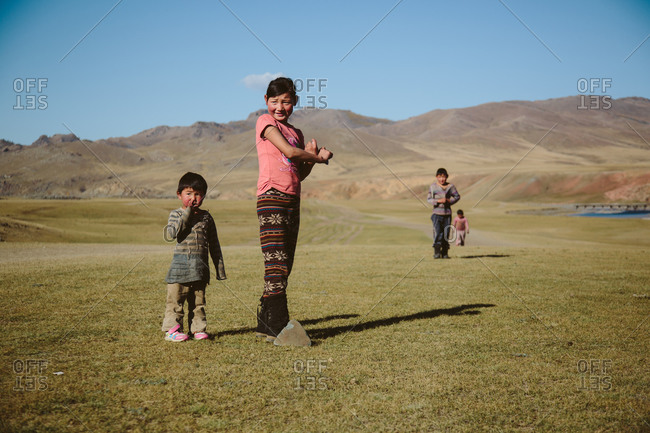 Mongolia - September 29, 2013: Playful Mongolian children in the beautiful landscape of the steppe