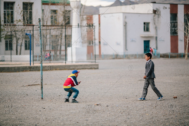 Mongolia - October 3, 2013: Two school friends, one in a suit and the other in casual wear, play outdoors