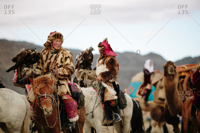 Bayan-Olgii, Mongolia - October 5, 2013: Kazakh Eagle Hunters on horseback with their birds at the annual Eagle Festival
