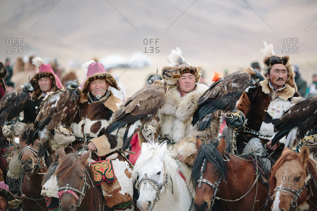 Bayan-Olgii, Mongolia - October 5, 2013: Row of traditional Kazakh Eagle Hunters with their eagles and horses at the annual Eagle Festival