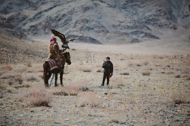 Bayan-Olgii, Mongolia - October 5, 2013: A Kazakh Eagle Hunter and his children prepare to compete at the Eagle Festival