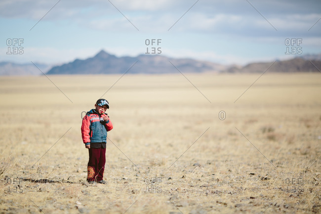 Bayan-Olgii, Mongolia - October 5, 2013: A boy with a candy treat in the desert landscape of Altai Tavan Bogd National Park