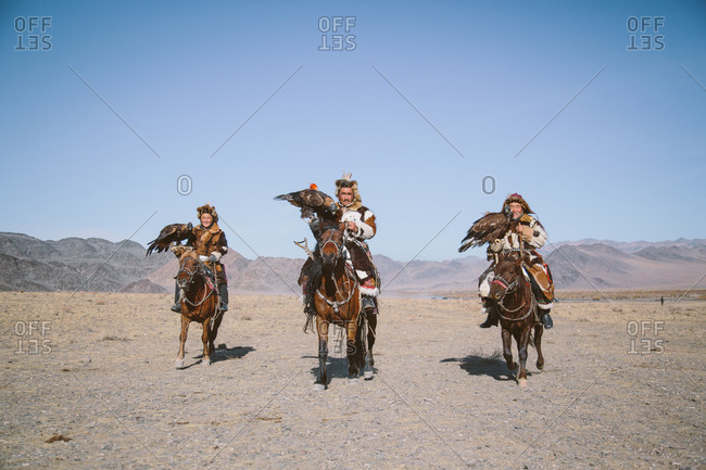 Bayan-Olgii, Mongolia - October 6, 2013: Three generations of eagle hunters arrive at the annual Eagle Festival