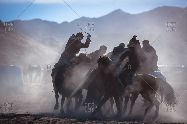 Riders compete in the game of kokbar, where each team attempts to wrestle a sheep skin from one another to score points