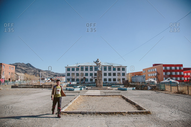 Olgii, Mongolia - October 9, 2013: A boy walks through the Soviet-built square with a statue of a communist general